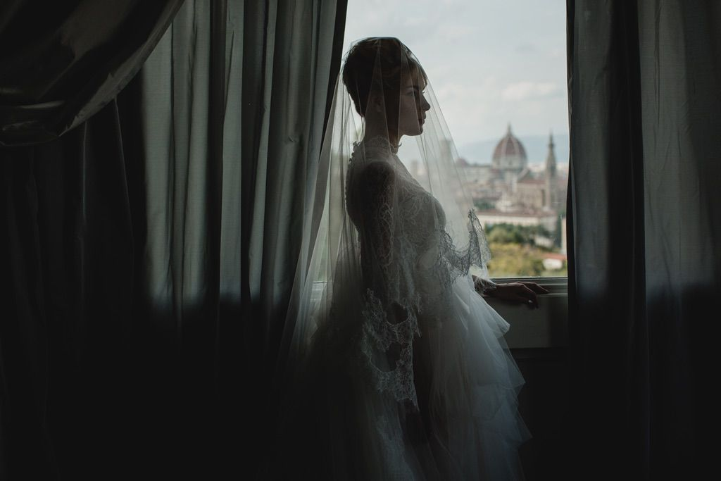 bride with long lace veil and her wedding dress in Firenze Italy