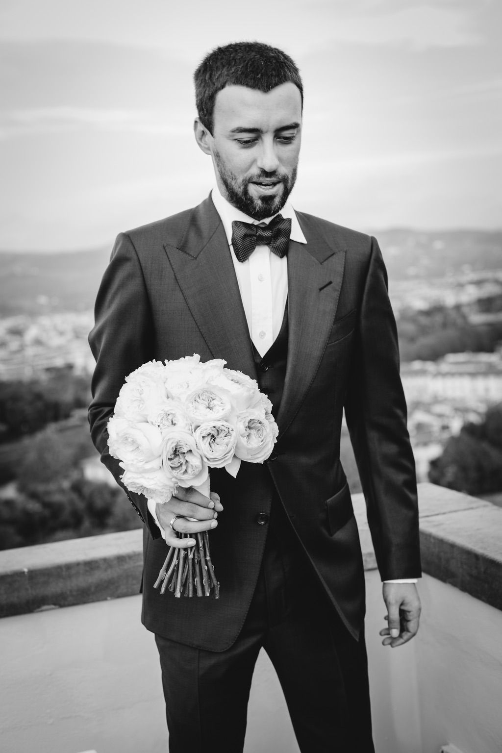 groom with a bouquet of peonies during his wedding in Italy